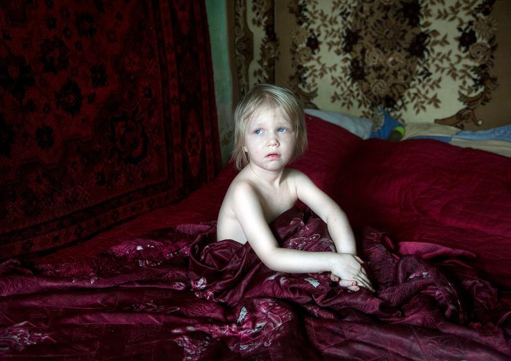 Life After Chernobyl. Daria, 3 years old, sits in her home in Vyzovka. Many families were relocated here after their villages were evacuated in the aftermath of the disaster. © Quintina Valero, Winner, LensCulture Emerging Talent Awards 2016.