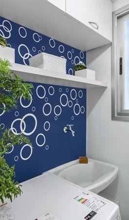 Parede da lavanderia pintada de azul com adesivos de bolhas brancas.