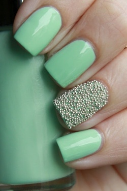 mint green nail polish with beaded accent on ring finger