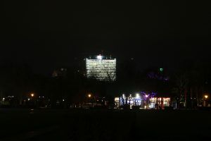 Brightly lit DB-Tower behind Großer Tiergarten in Berlin. That 'pitch black' park is bright enough to read a newspaper. Foto: Annette Krop-Benesch