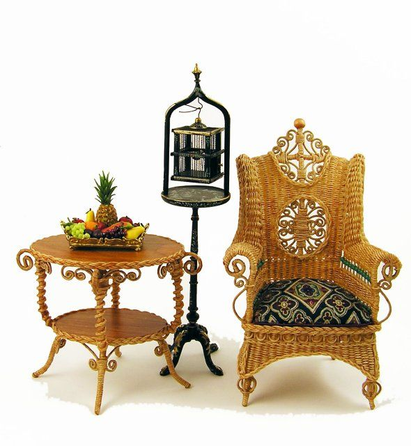 Beautifully detailed hand-crafted Natural wicker Wing Chair by Rhea Strange $495 (see closeup below)  Natural wicker detailed side table by Rhea Strange $195  A assortment of fruit on a fancy gold serving tray by Lola $65  Bird cage and stand hand painted in black with gold by Bespaq $75