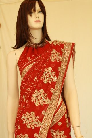 Lovely red georgette saree with all over embroidery. This saree already comes with a halter neck blouse and a traditional saree blouse that can be semi custom fit on request if possible. Gold tissue zari piping is is all along the saree edges creating a very rich look.   Saree needs silky petticoat. Please add measurements in notes when you buy these optional items and we can custom make it for you.