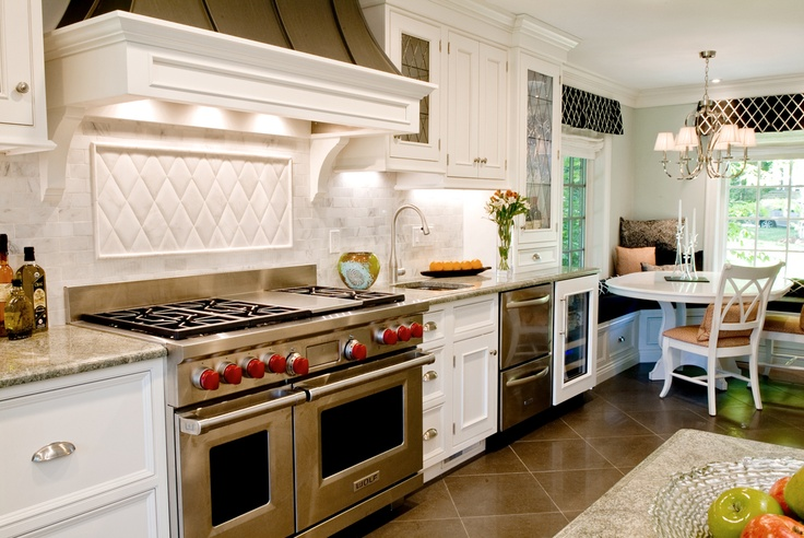 Our heart skips a beat for this elegant white kitchen. A framed, quilted tile backsplash inset adds a subtle accent over the pro-style range, while pillows and valances add texture and color to the room.    Designed By: Westborough Design Center  Westborough, MA  Photo by : Carol Savage