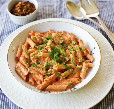 Penne with Creamy Vodka Tomato Sauce  •1/4 cup olive oil  •4 cloves garlic, diced    •1/2 teaspoon red pepper flakes   •sea salt  •tomato puree ( 28 oz)  •1 pound dried Penne ( GF folks I am a huge fan of BioNatura Pastas)    •1 cup heavy cream   •2 tablespoons vodka   •1/4 cup fresh Italian parsley leaves cut with scissors