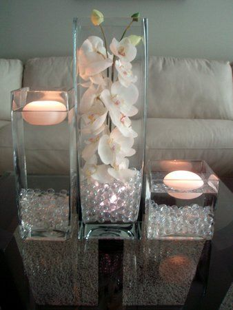 Square vases of various sizes, crystal rocks, candles, flowers