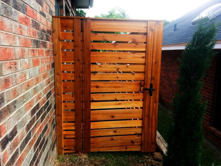 """This Carrollton homeowner wanted a modern looking fence instead of your traditional vertical style, so we suggested a horizontal cedar fence. This project included 4 x 4 cedar post with horizontal 5 1/2"""" smooth cedar rails & 3"""" smooth cedar rails to give a nice clean modern look. We topped it off with a 1 x 6 cedar topper to frame out the fence and finished it with one sleek looking gate."""