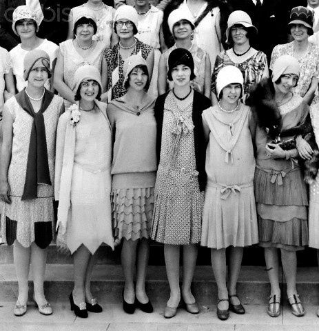 Everybody in this picture were wearing the same style, which are dropped waist dress, high heels, clouche hat and bobbed hair style. Those are craze in this time period. Also, some of theme were wearing pearl necklace