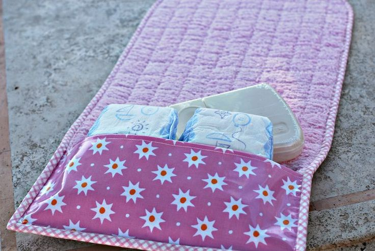 Diaper changing mat with holder for extra diapers and wipes. folds up into a small clutch - great for baby gifts