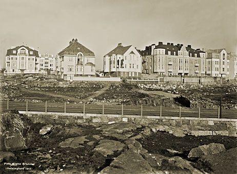 Edessä poikittain kulkee Speranskintie (nykyään Meritie). Lähempänä sijaitseva talorivistö seisoo Ehrensvärdintiellä ja täysin vasemmalla oleva talo on Armfeltintiellä. Signe Brander 1911.