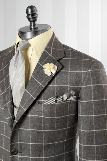 Groom in ivory shirt and orange and green tie and pocket square