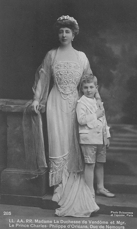 Henriette, Duchess of Vendome and her son, Prince Charles-Philippe d'Orleans, Duc de Nemours. The Duchess' dress shows the slimmer line and waistless look of 1910. Her dress also has a thoroughly Renaissance-looking crescent neckline
