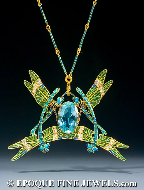 René Lalique. Dragonfly Pendent, c 1903, depicting four dragonflies, with greenish-blue enamelled legs and wings with complex gold veining set with diamonds and green and blue plique-à-jour enamel, centering a large oval aquamarine; on a rod and link enamelled gold chain.