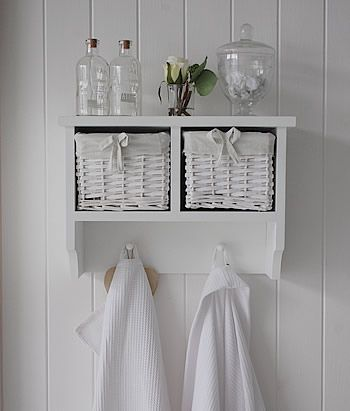 A white wall shelf with 2 baskets and hanging pegs. Hall furniture