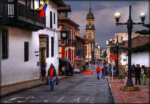 La Candelaria, Bogotá D.C., Colombia. A la izquierda, la Casa de la Moneda del Nuevo Reino de Granada, se fundó en 1621 (en la calle 11 con 4.ª). Ha tenido varias transformaciones. Son las 10:40 a.m., el reloj fue pedido por el Banco de la República a la empresa Electric Time Company, sucursal de Nueva York. Empezó a funcionar el 25 de abril de 1955, al fondo la torre norte de la Catedral Primada.