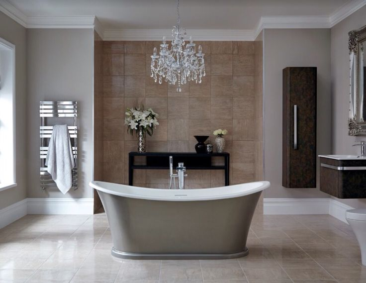 This elegant bathroom uses symmetry and colour to create the focal point of the free standing bath with chandelier above. The styling is beautiful. Photo credit- bathstore, UK