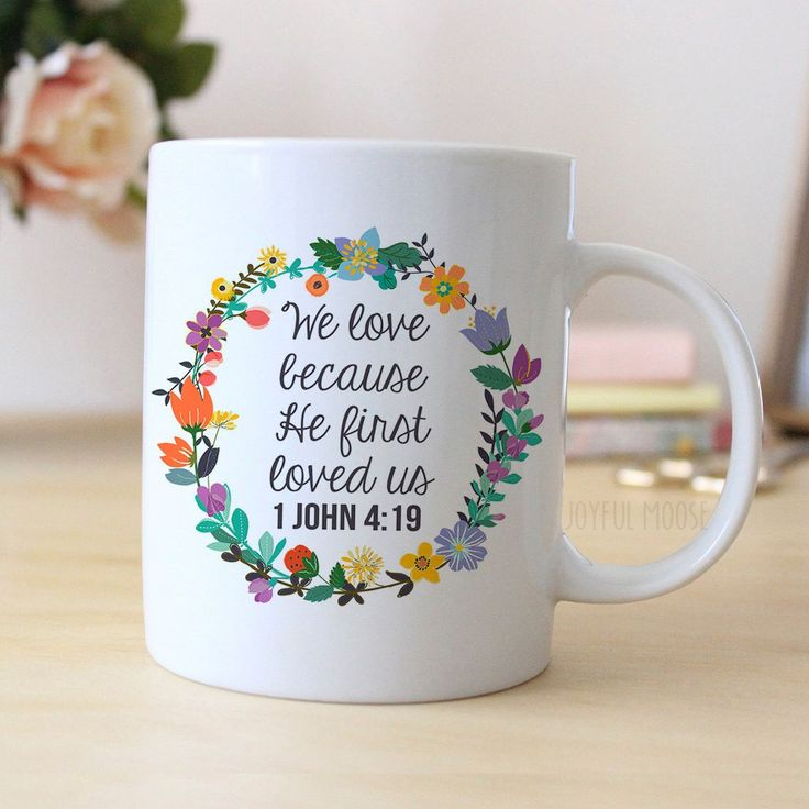"Coffee mug says ""We love because He first loved us"" along with a floral wreath…"