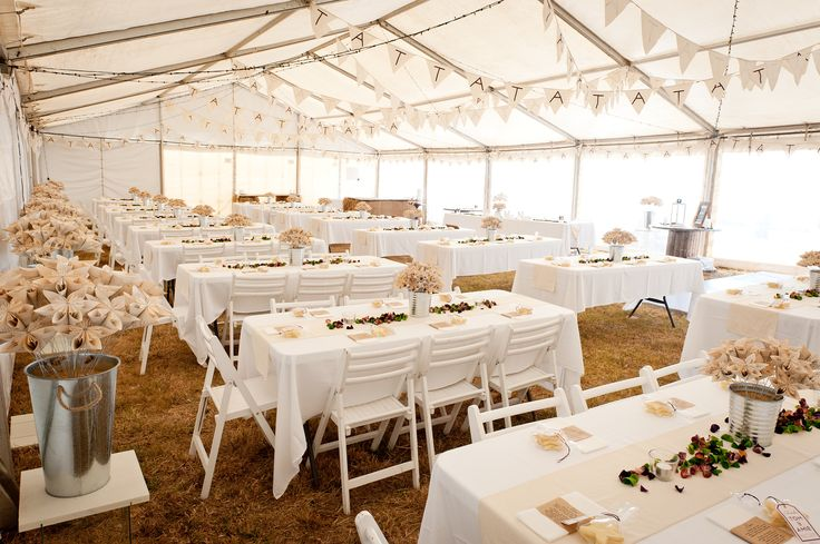 Rustic wedding tables. Handmade paper flowers. Coloured, scented wood curls. Dark purple and apple green. Calico bunting