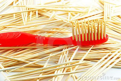 Red toothbrush on the toothpicks background