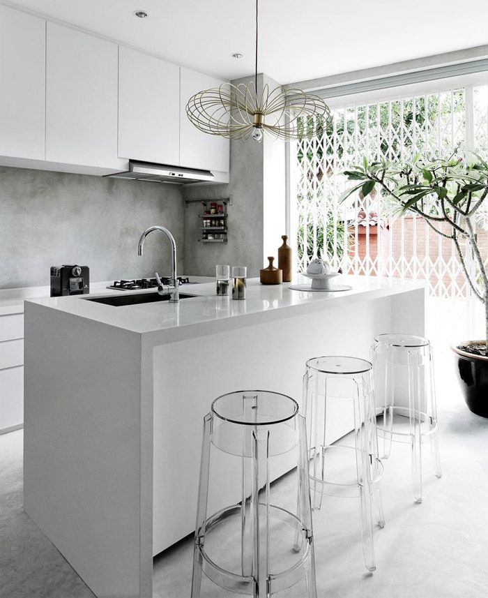 Modern white kitchen with bar / kitchen island with sink and clear plastic stools.