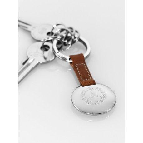 Portachiavi, nastro in pelle nera o marrone con cuciture di contrasto bianche, ciondolo color argento con logo storico del 1926;