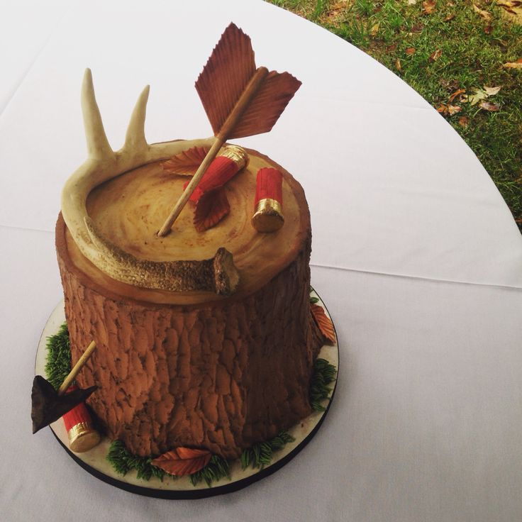 A hunting themed grooms cake complete with deer antler, shotgun shells and arrow on buttercream bark.