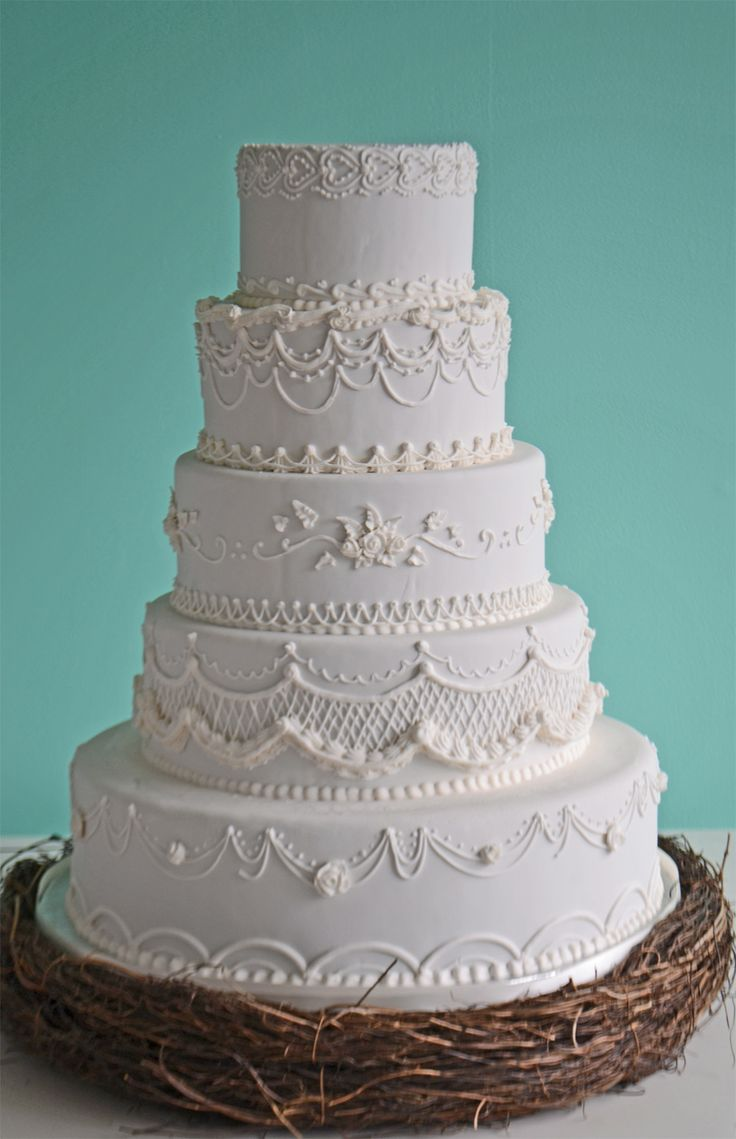 Pretty white-on-white five tiered wedding cake set on a nest for a spring wedding. Cake by Bake Sale.