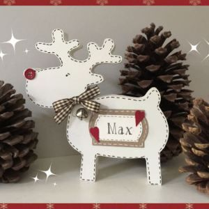 A 15cm freestanding personalised reindeer. Made from 18mm MDF and painted in Annie Sloan Old White chalk paint. Finished with a cream personalized label, set on top of a larger kraft label. The name is handwritten pen. The festive look is completed with a red button nose and a matching brown and cream gingham bow and jingling silver bell.
