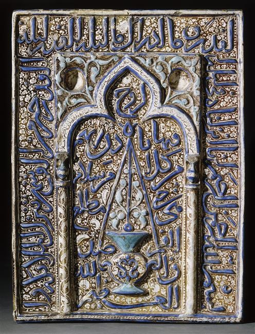 Wall tile in the form of a mihrab 13th century Kashan, Iran Fritware, moulded and lustre-painted overglaze decoration, opaque glaze, colour highlights