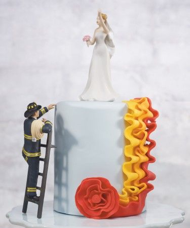 """To the rescue fireman groom figurine  This Groom is all decked out in his firefighting gear and climbing a ladder to get to his Bride.  He is held in place by two pegs on the ladder so simply lean him up against one of the bottom tiers of your wedding cake and he is all set to rescue his Bride.  Product Material:Hand Painted Porcelain    Size: 6 1/4"""" H  Bride sold separate. - See more at: http://www.favorsdepot.com/to-the-rescue-fireman-groom-figurine.wedding#sthash.zbXznaQn.dpuf"""
