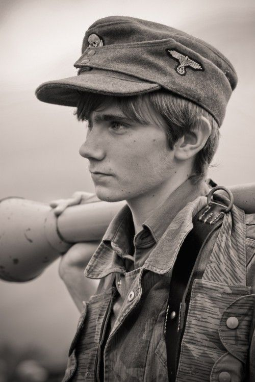 A young WWII reenactor in a German uniform holds a panzerfaust, the predecessor to the rocket launcher, at a living history event in Manassas, Virginia. October 2009.