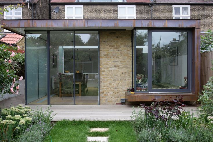 From the outside view you can see that the steel surround, with a rusted finish, frames the Minimal Windows meeting the supporting beams and structural glass window and window seat.