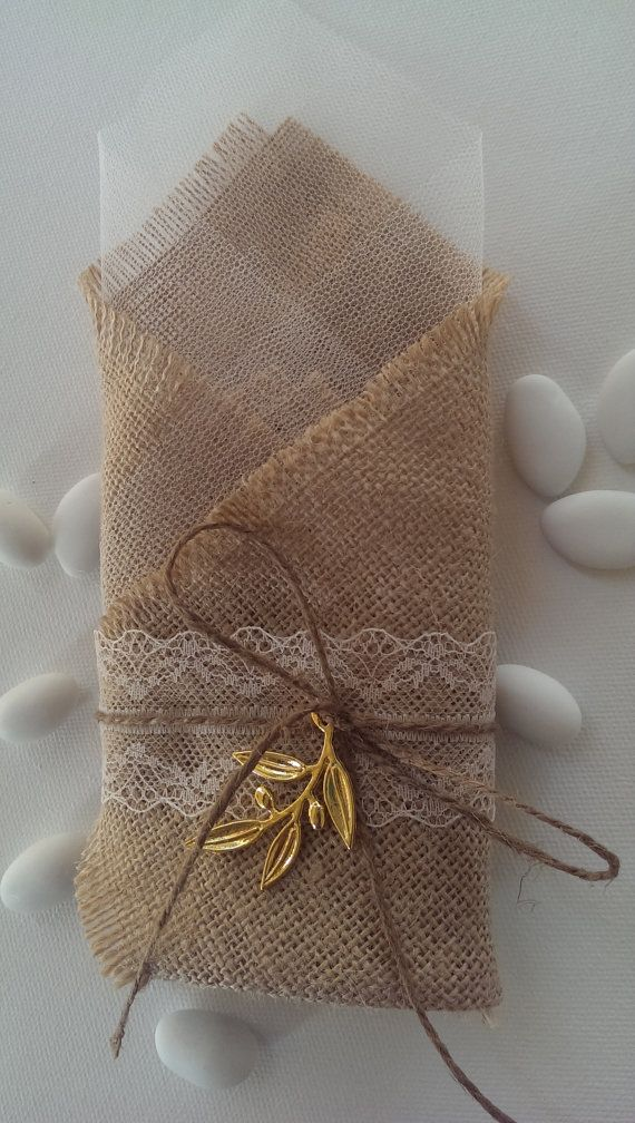 Handmade burlap wedding favor/bomboniere decorated with an olive leaf in gold color and lace ribbon.