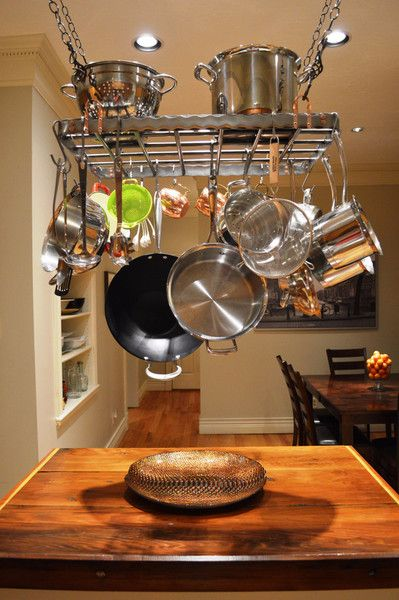 This one-of-a-kind modern hanging pot rack is made from polished steel. Its clean straight lines make it ideal for any modern style kitchen. It pairs exceptionally well with stainless steel appliances & cookware. This rack will not only be the focal point of any kitchen but will provide practical & usable space for those awkward pots, pans & large kitchen utensils. Copper rivets and chain loops have been added to the corners of the rack to provide accents that compliment the b...