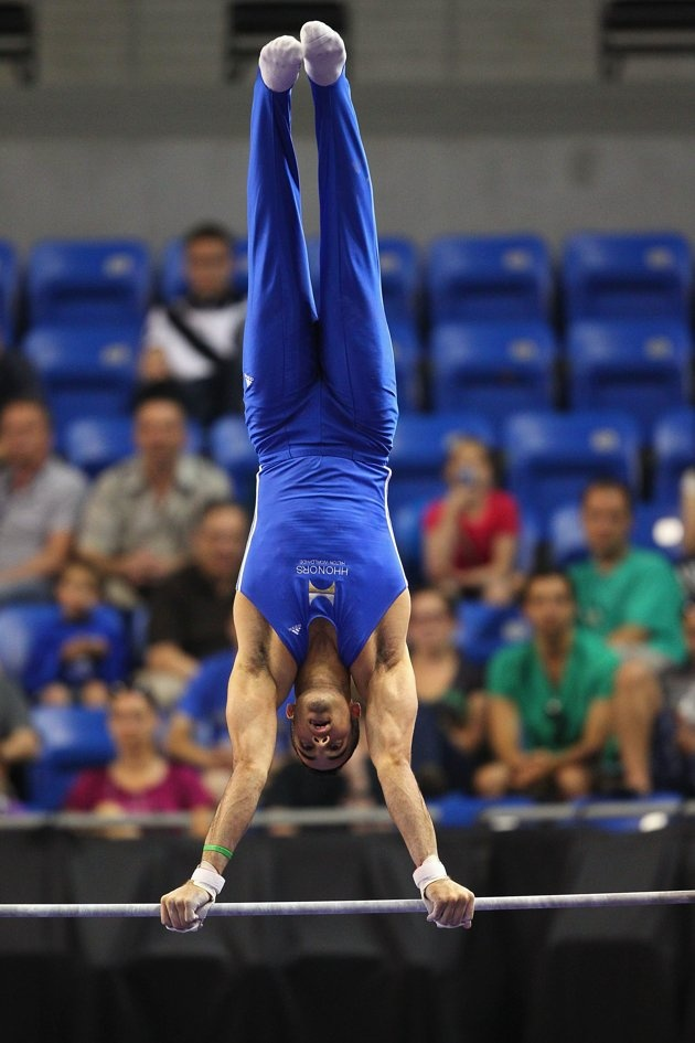 Danell Leyva holds a handstand on the high bar during the 2012 Visa Championships finals, the qualifier for the USA Gymnastics Olympic Trials.  Leyva won the event title.