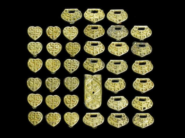 Thirty-eight Byzantine gilt silver belt fittings Eastern Europe - Central Asia, circa 10th-14th Century A.D. Mostly heart-shaped or D-shaped with a central apex, all with gilded surfaces similarly decorated with foliate sprigs, the underside with three attachment studs, 23mm longest, and one of rectangular form with rounded end and fleur-de-lys motifs, with four studs on the underside, 1½in (3.8cm) long (38) Ex private collection