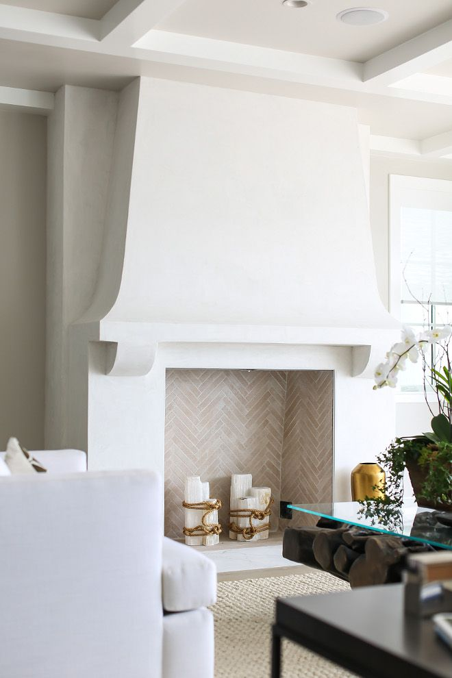 "Fireplace: Isokern custom masonry fireplace built on site with herringbone firebrick cut down to 2"" x 8"" with white grout. Fireplace face is white smooth stucco finish to resemble a plaster wall."