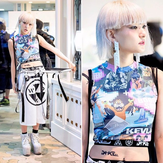 "Japanese model/DJ/YouTuber @darayunya on the street in Harajuku with an asymmetrical bob hairstyle, a DVMVGE crop top, DVMVGE ""WMD"" wide leg pants, earrings by the Japanese brand MYOB, an MYOB harness, and YRU platforms."