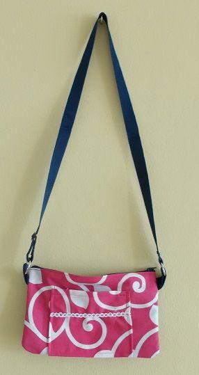 """carterita 4""""x7"""" mitad mahón tela estampada rosada  y blanca, con bolsillo delantero, cierre de zipper y mango largo con ajuste"""
