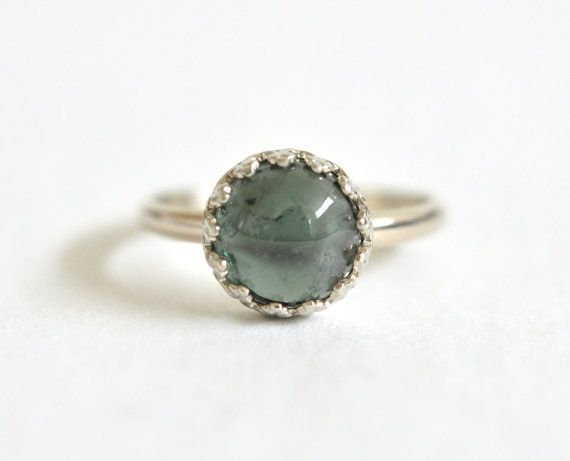 This green tourmaline ring would be an extraordinary diamond-alternative engagement ring! The gemstones soft blue-green color contrasts beautifully with the airy white gold crown bezel. The translucent tourmaline has unique inclusions, which add an organic quality to the stone, and sits perfectly in this dainty setting. An 8mm natural green Tourmaline gemstone is set in a crown bezel 14k white gold ring. This item is handmade to order and will take 1-2 weeks to complete.  Available in whole…