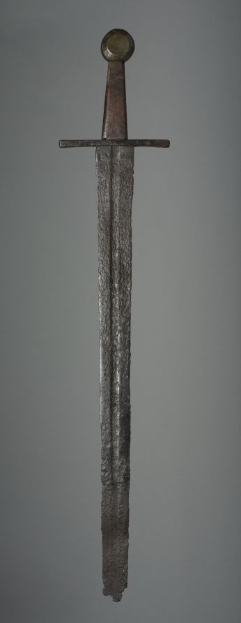 Sword, c. 1350 Germany (?), 14th century iron; wood grip and brass pommel replacements, Overall - l:79.40 cm (l:31 1/4 inches) Wt: .90 kg Blade - l:62.90 cm (l:24 3/4 inches) Quillions - w:15.30 cm (w:6 inches) Grip - l:10.80 cm (l:4 1/4 inches).