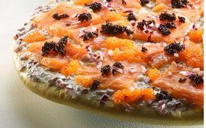 Hvid pizza med røget laks og stenbiderrogn I denne opskrift bages pizzabunden, hvorefter den bage bund smørres med fraiche og fyldes med laks, rogn, løg og citron.