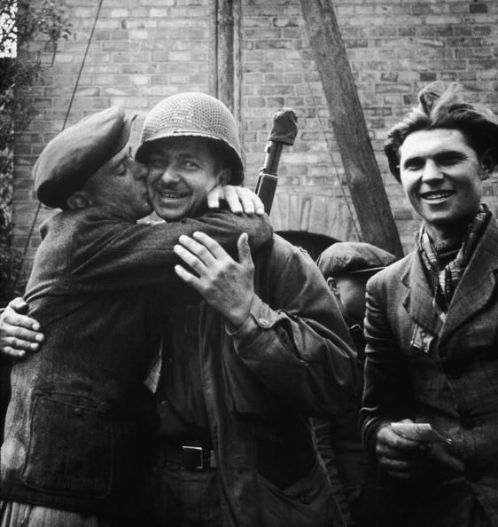 April 1945: A Polish man embraces an Allied soldier, kissing his cheek, after being liberated from a Nazi forced labor camp in Germany during World War II. (Photo by Tony Vaccaro/Hulton Archive/Getty Images)