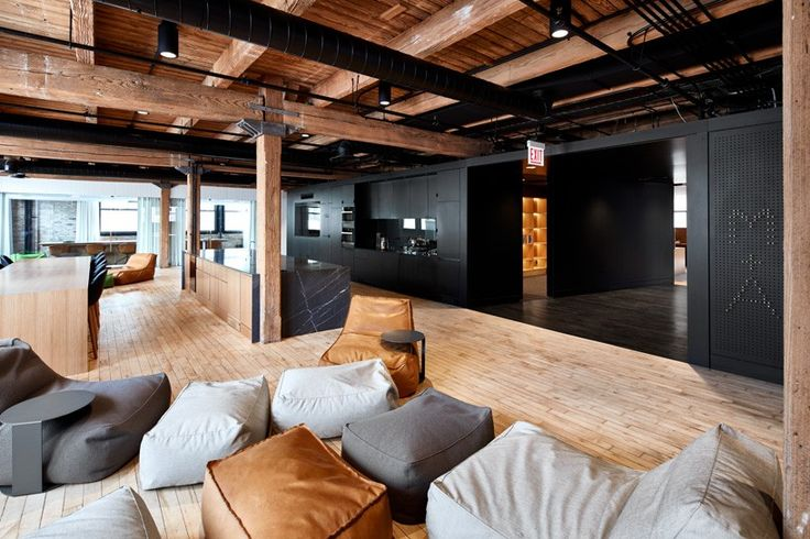 an entire floor of a former warehouse has been transformed into a workspace featuring a full-scale batting cage and comfortable breakout areas.