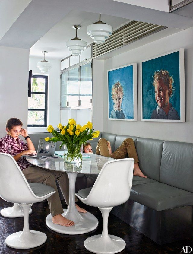James, left, and Rex do homework at the kitchen's Saarinen table, under the gaze of Simon Birch oil portraits of their younger brothers; the banquette and Saarinen chairs are cushioned in a DeLany & Long outdoor leather.