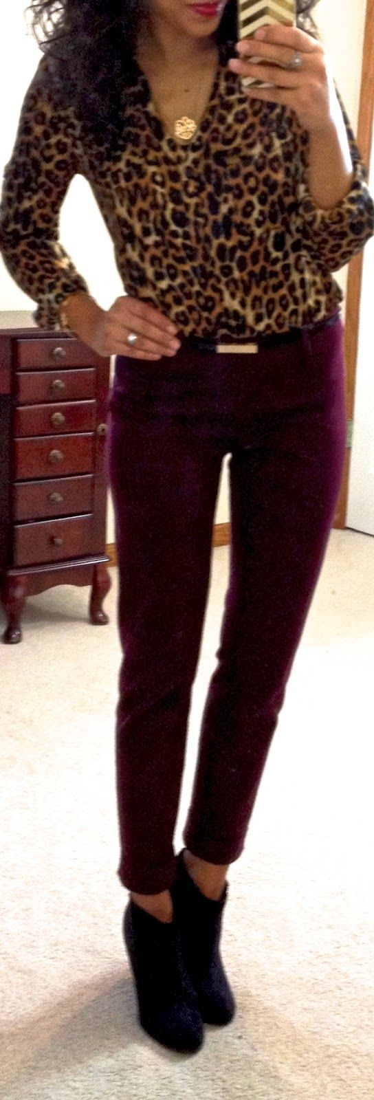 leopard print blouse, maroon pants, and ankle boots.