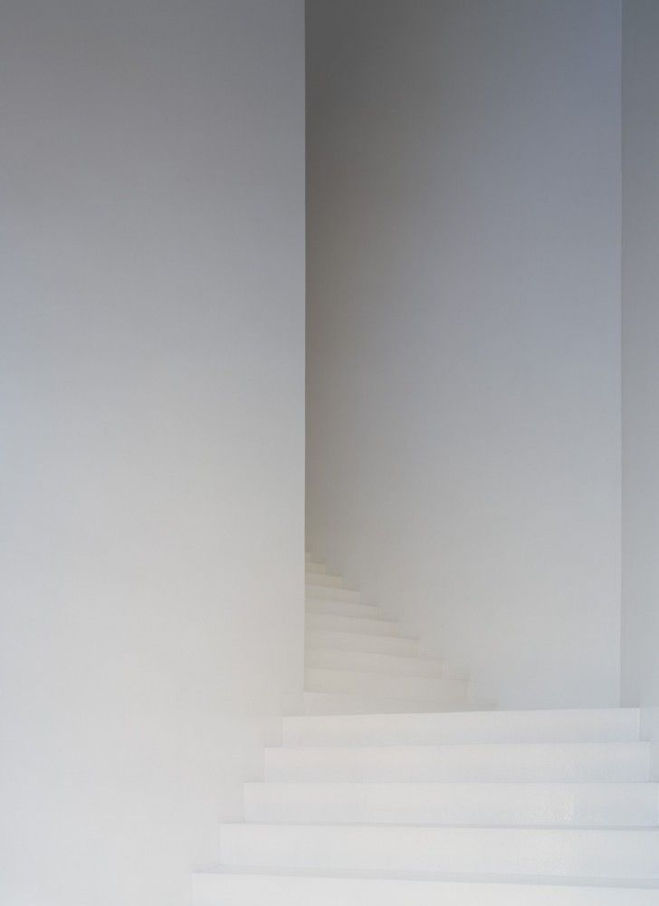 White staircase inside the Casa dos Cubos by EMBAIXADA arquitectura.