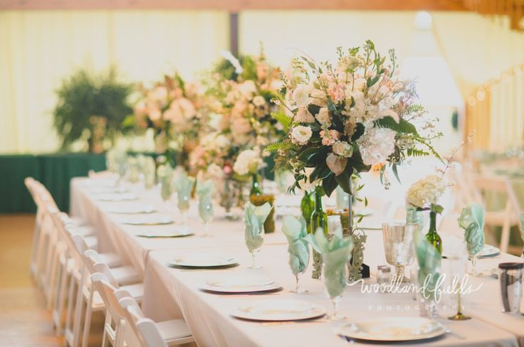 the head table is lined with iron pedestals holding a beautiful lush arrangement of white hydrangea, chocolate queen anne's lace, white queen anne's lace, white lisianthus, mini pink carnations, peach stock, fern, jasmine trails, white fountain grass, white wax flower and magnolia branches