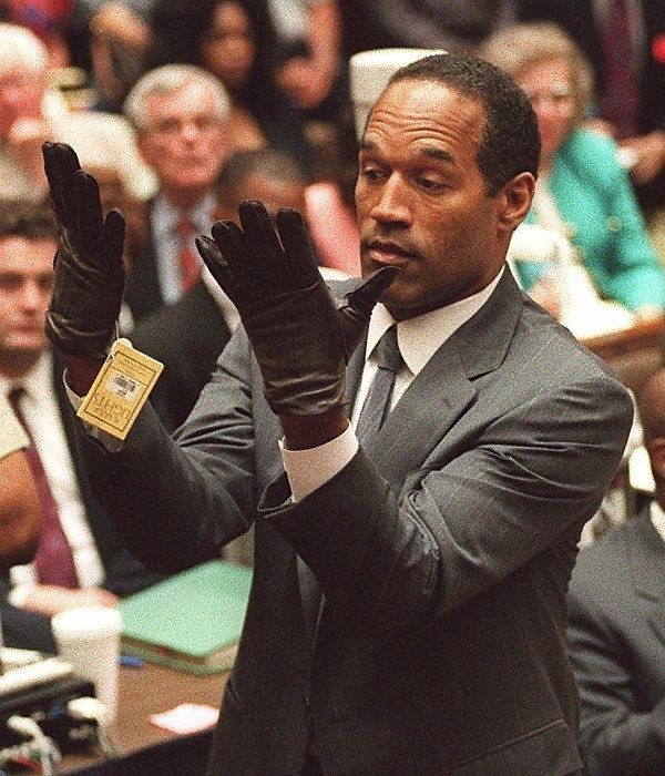 "June 15, 1995: OJ Simpson showing the jury that ""If [the gloves don't] fit, you must acquit"" in the case of Nicole Brown."