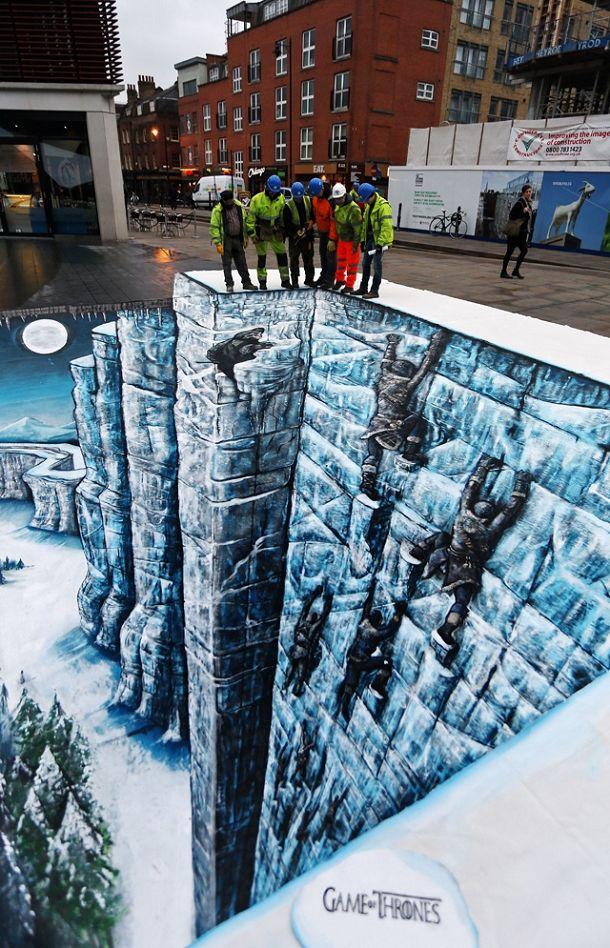 """Un trompe-l'œil géant de Game of Thrones a été peint sur le sol à Londres afin de faire la promotion de la sortie DVD et Blu-Ray de la saison 3 de Game of Thrones. La chaîne HBO a fait appel aux artistes Joe&Max pour la réalisation. La peinture au sol représente le fameux """"Mur"""" de neige de la série télévisée et donne une illusion de perspective. Ce trompe-l'œil gigantesque peint dans le quartier Bishops à Londres mesure 10 mètres sur 7 mètres."""