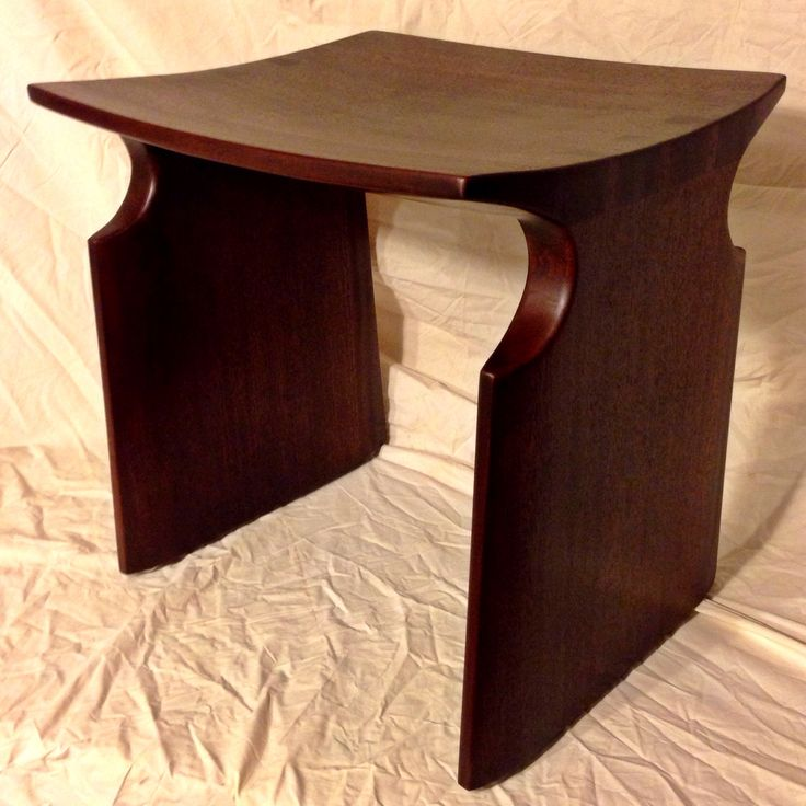 Renwick Stool: a variation on a design by David Ebner, this sturdy dovetailed stool has a comfortable carved seat and sinuous curves. Made from a single board of African Sapele, finished in dark java brown.